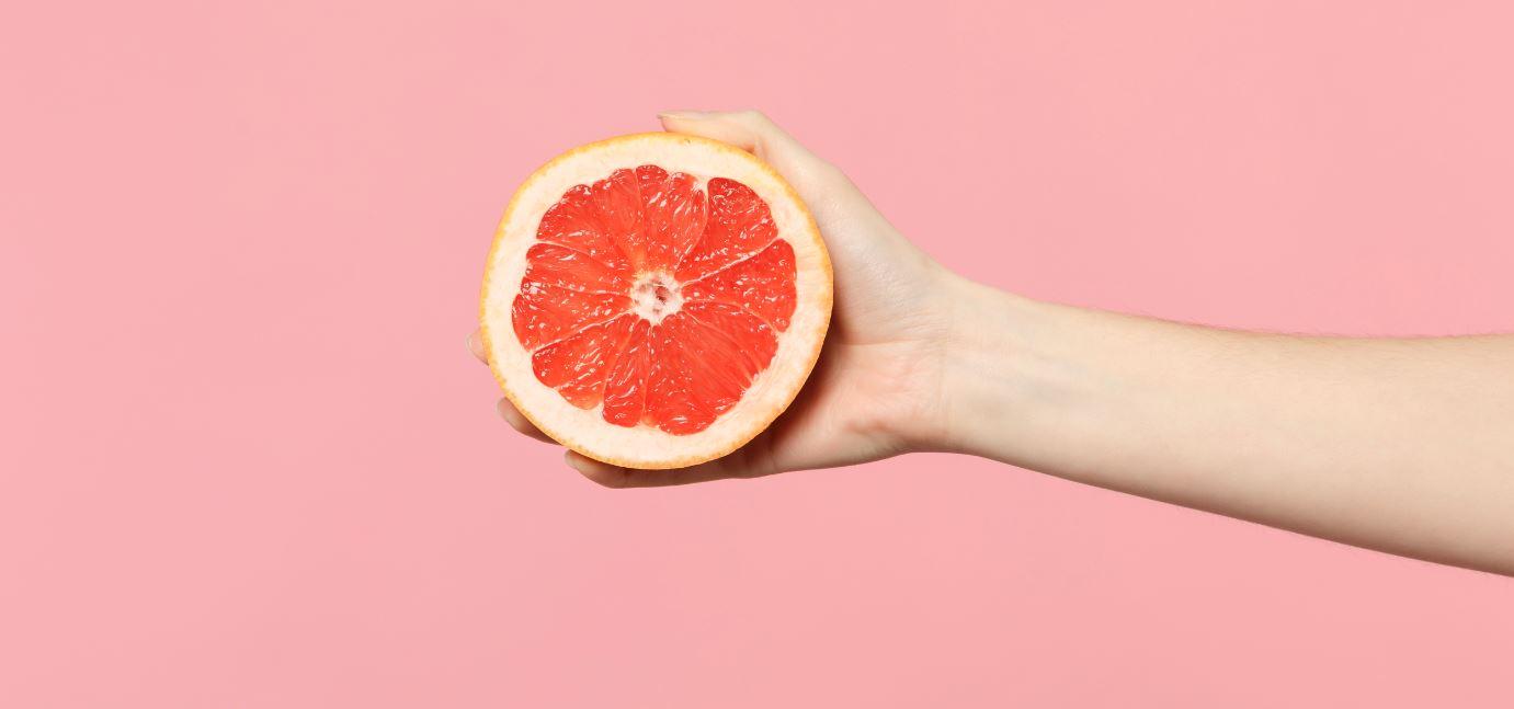 weibliche Hand hält halbierte Grapefruit vor rosa Hintergrund