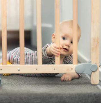 Baby hinter Treppengitter