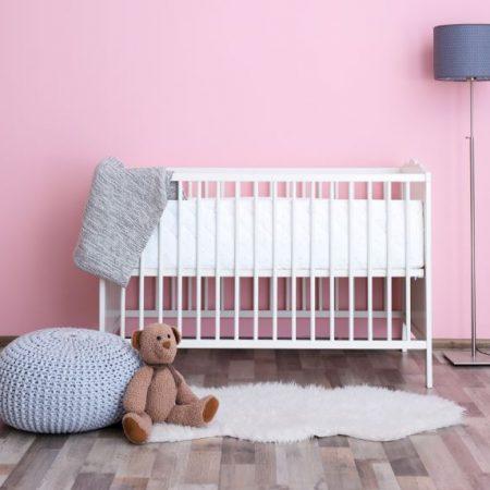 babybett vor rosa Wand