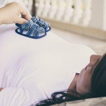 Frau hält Babyschuhe auf ihrem Babybauch