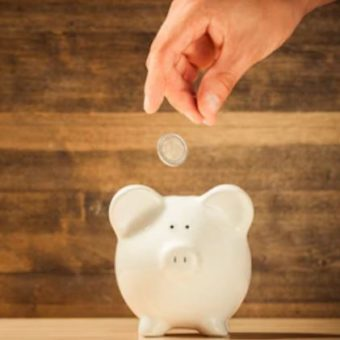 Hand wirft Geld in Sparschwein