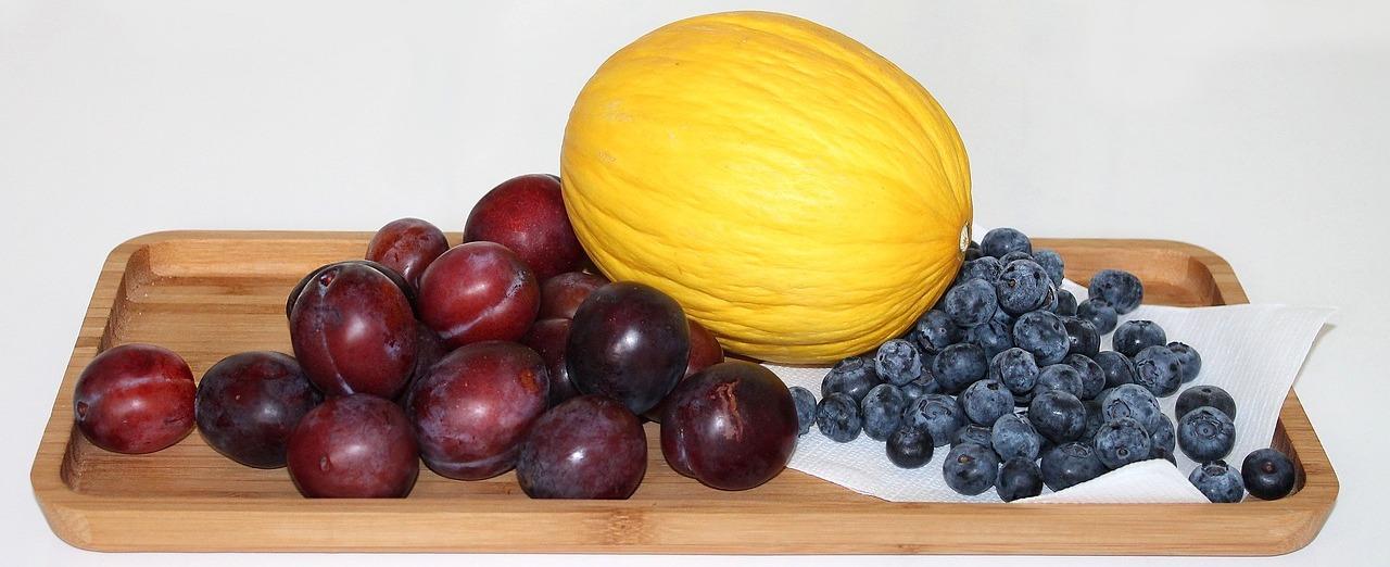 Brettchen mit Obst: Pflaumen, Honigmelone und Heidelbeeren