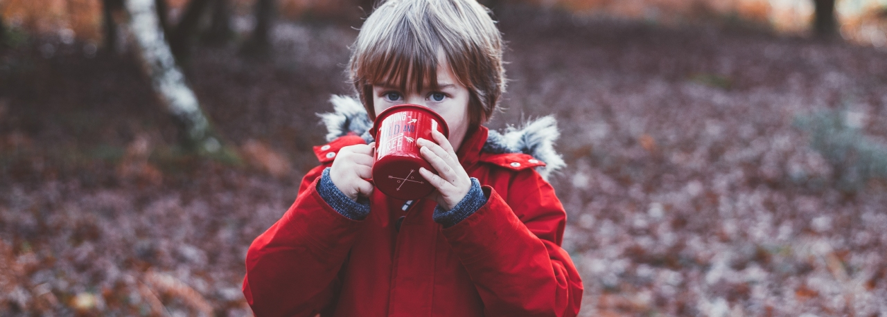 Junge draußen mit Tee