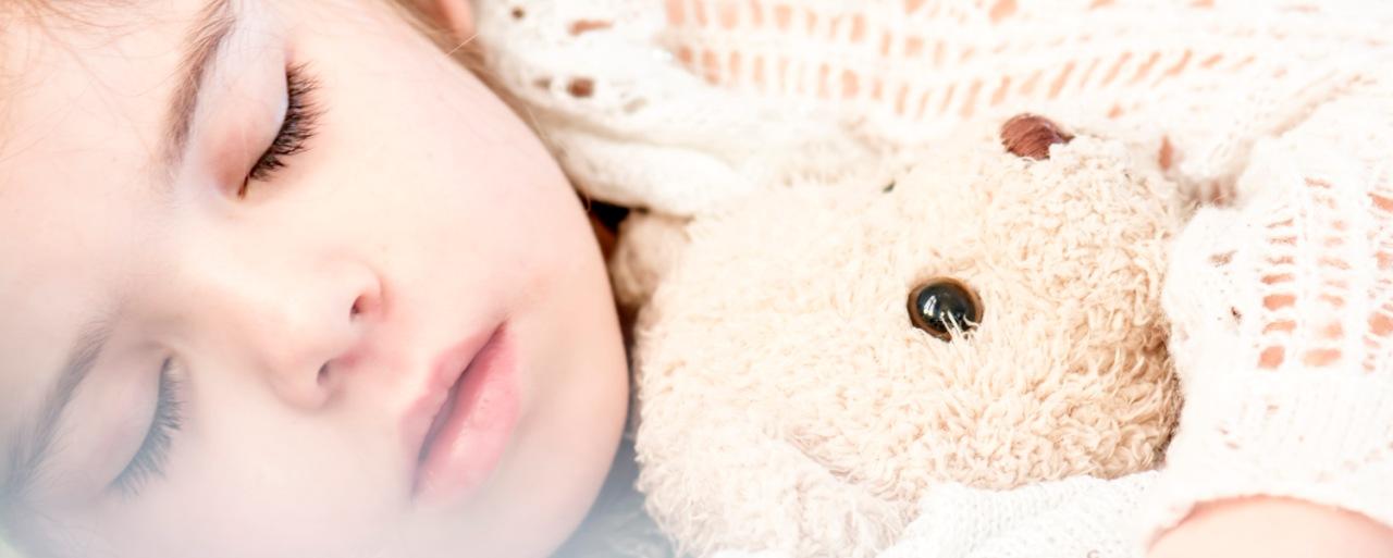 Kleinkind schläft und kuschelt mit Teddy