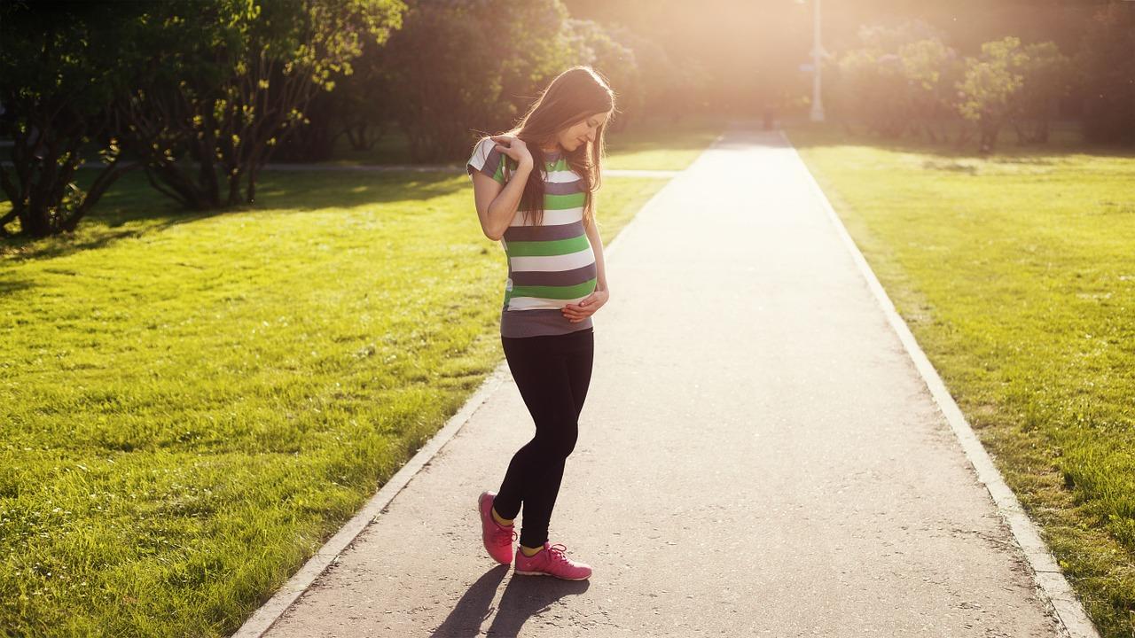 Schwangere geht im Park spazieren