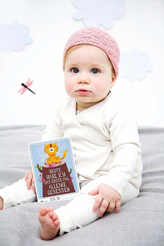 Sitzendes Baby mit Meilensteinkarte
