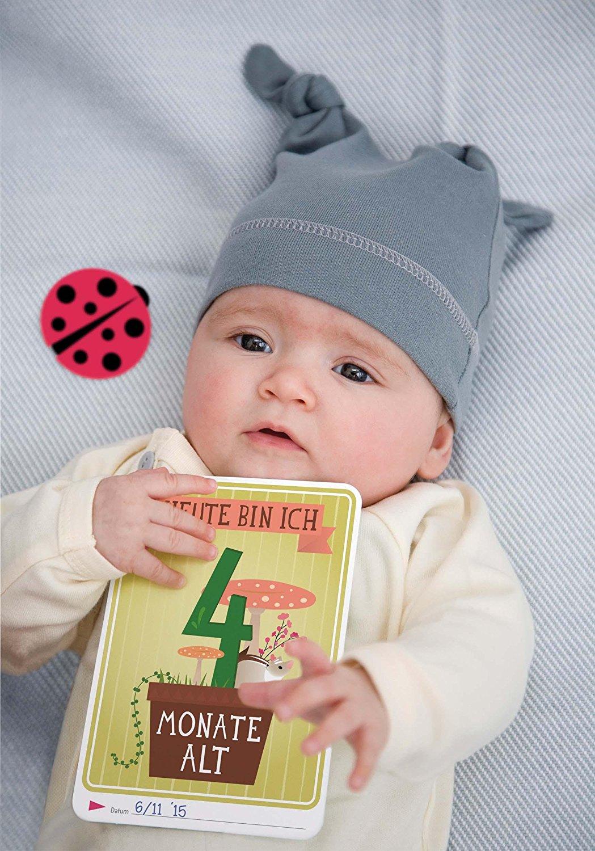 Liegendes Baby mit Meilensteinkarte in der Hand