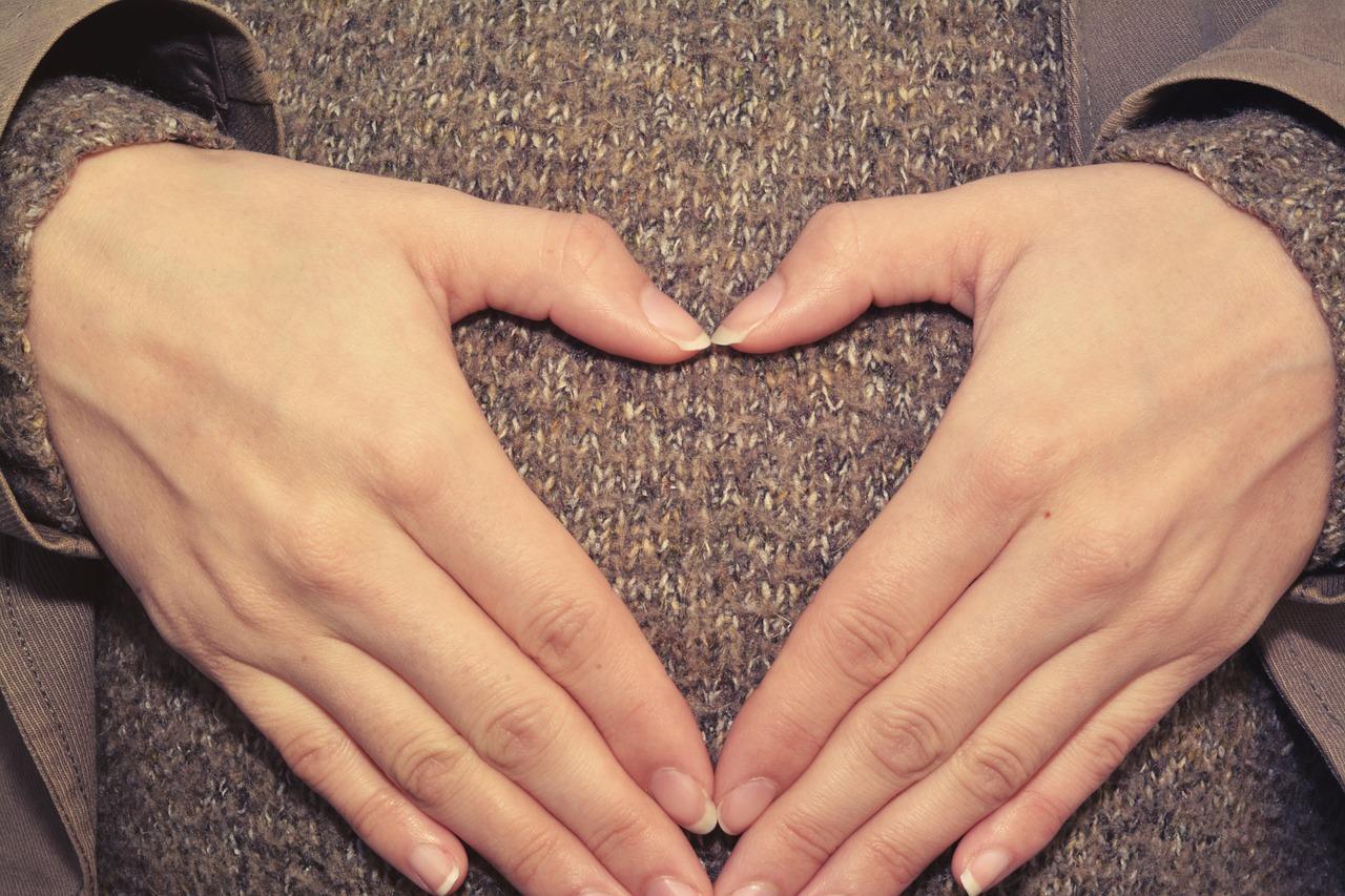 Herzhände auf dem Bauch