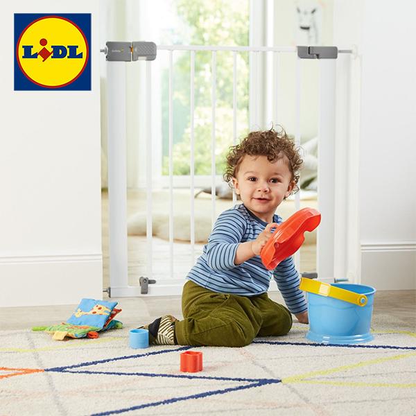 Kleinkind sitzt vor LIDL Türschutzgitter