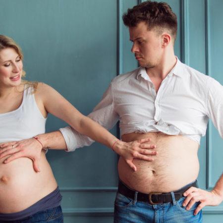 Schwangeres Paar hält sich die Bäuche