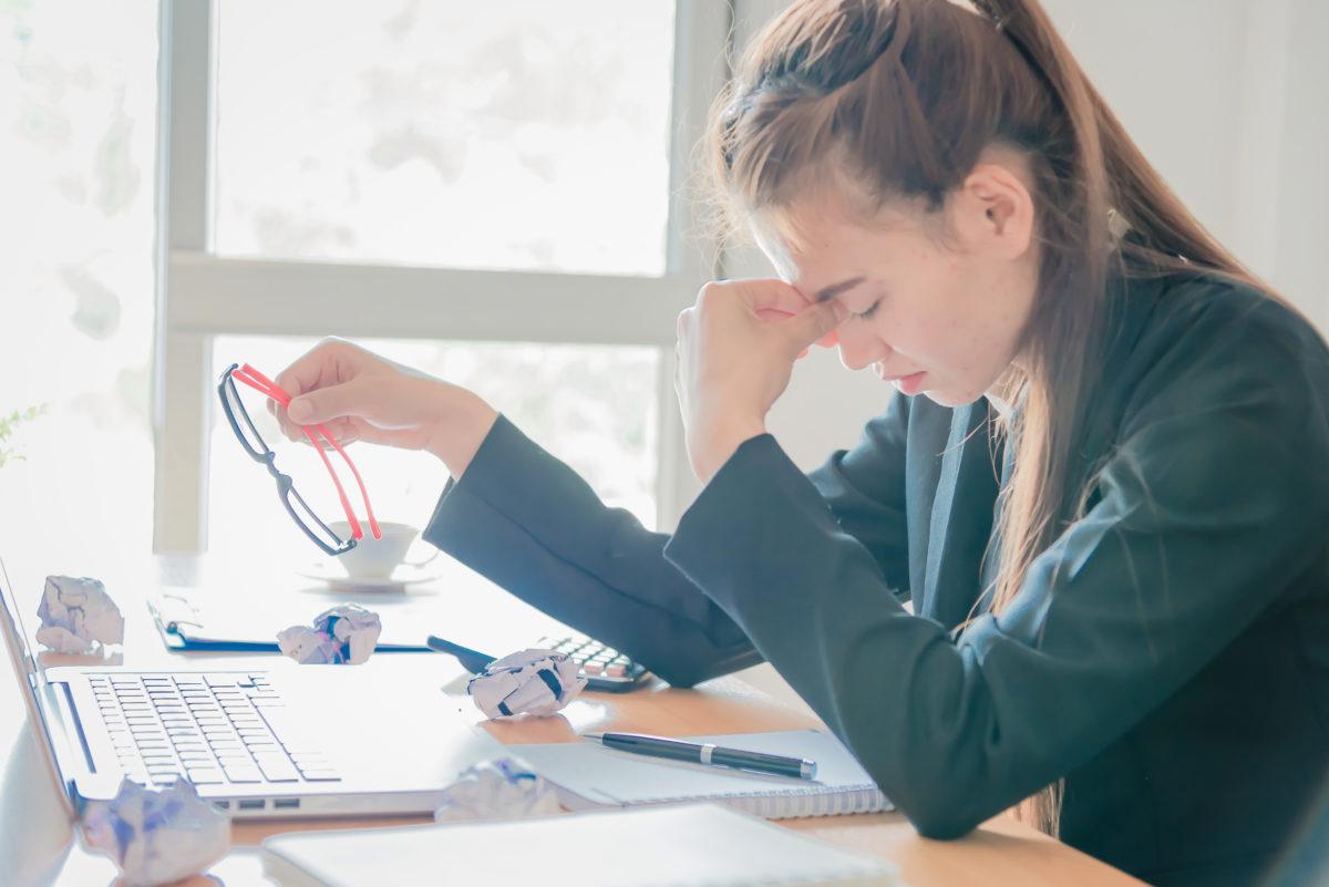 Frau sitzt traurig bei der Arbeit