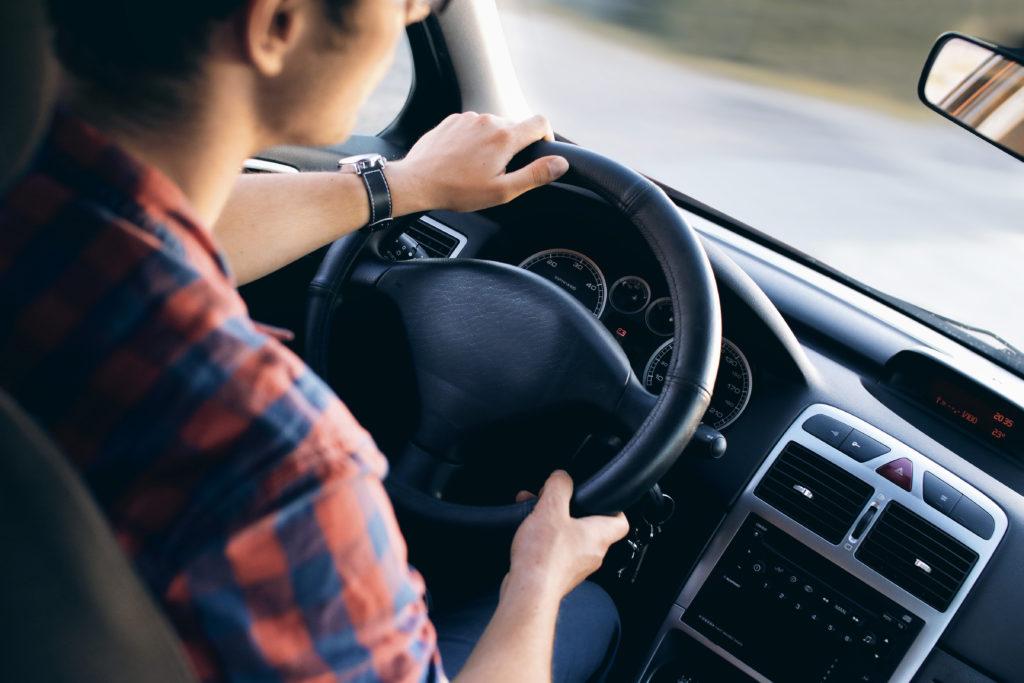 Mann fährt Auto, sitzt am Lenkrad