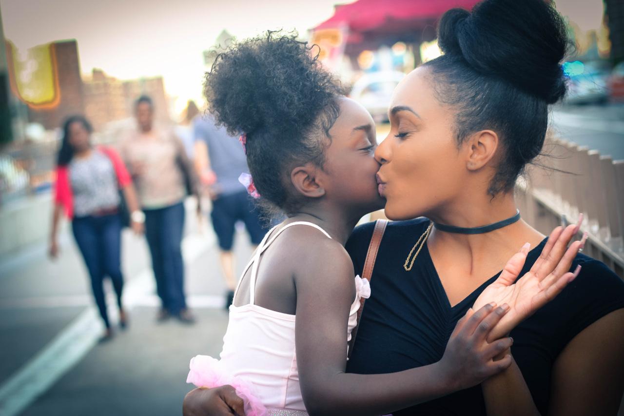 Küsschen von Mutter und Tochter