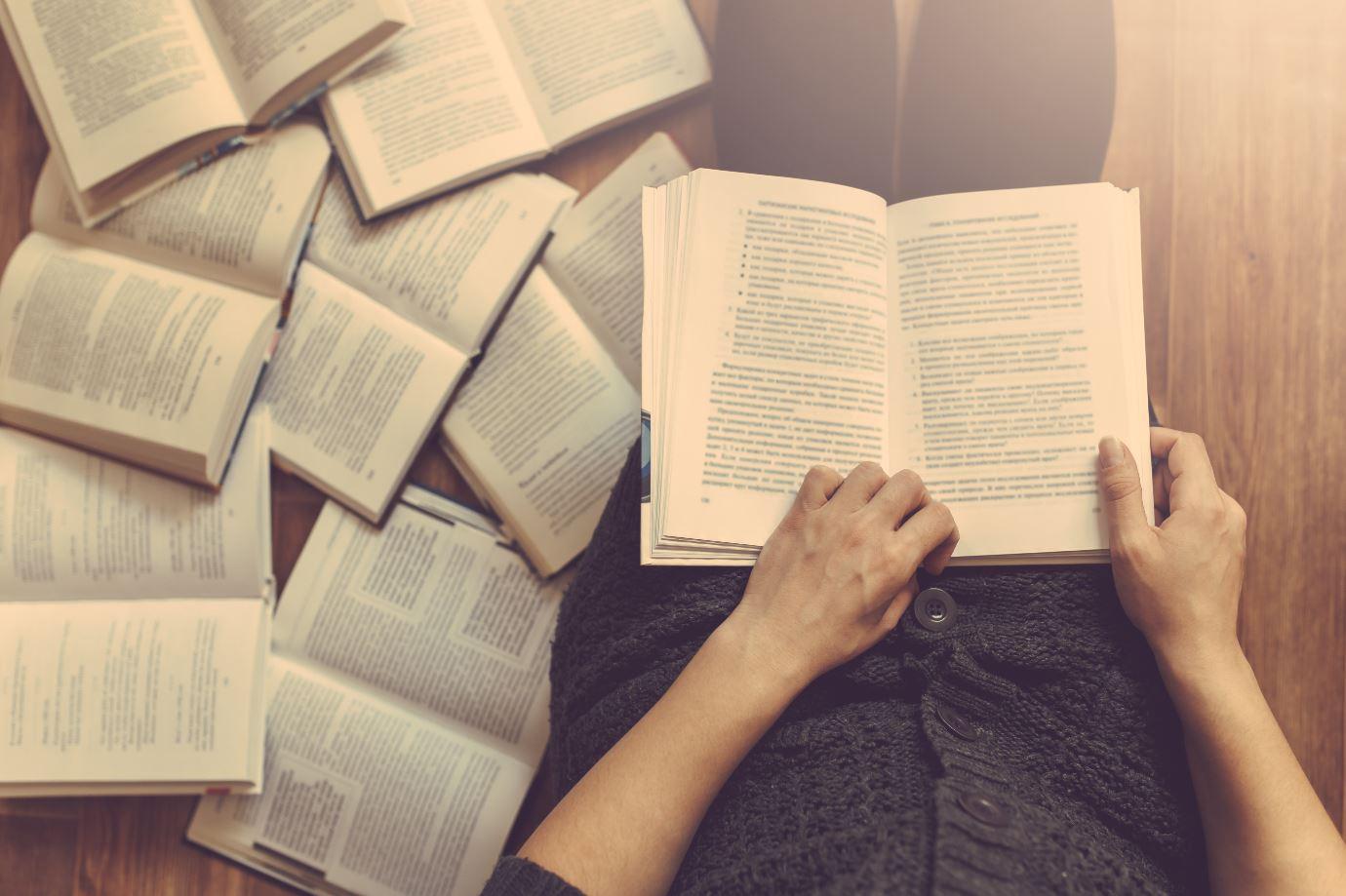 Frau mit vielen Büchern vor sich