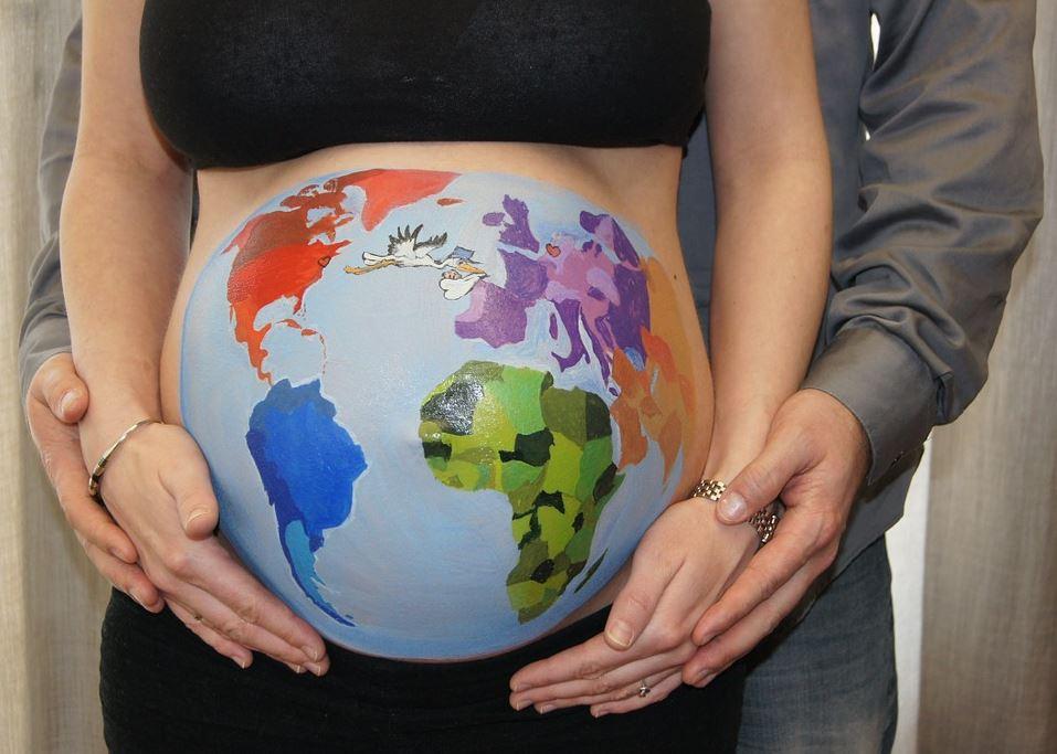 Babybauch einer Schwangeren mit bunter Weltkarte bemalt