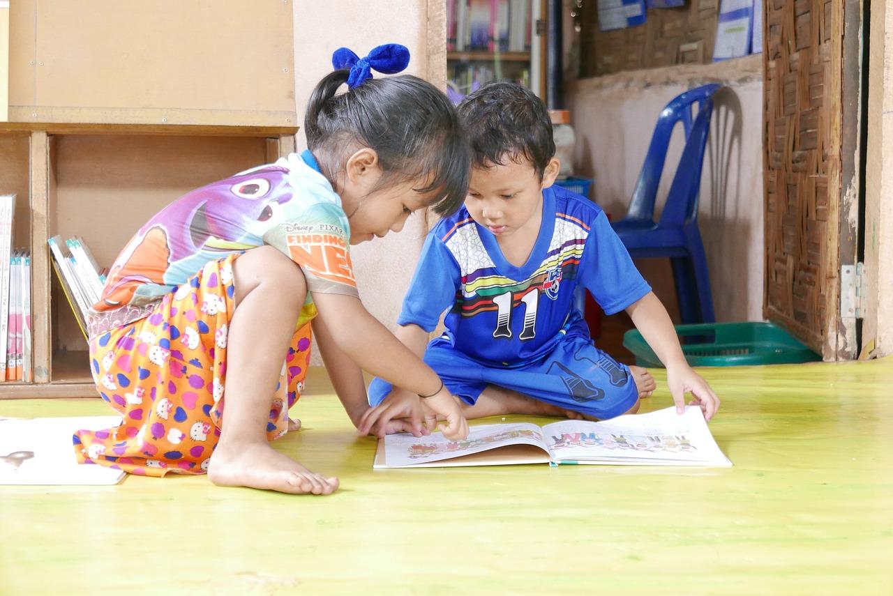 zwei Kinder lesen ein Buch