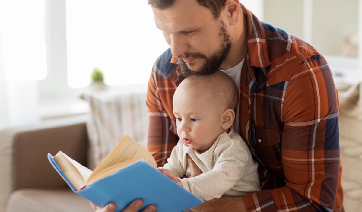Vater liest mit Baby in einem Buch