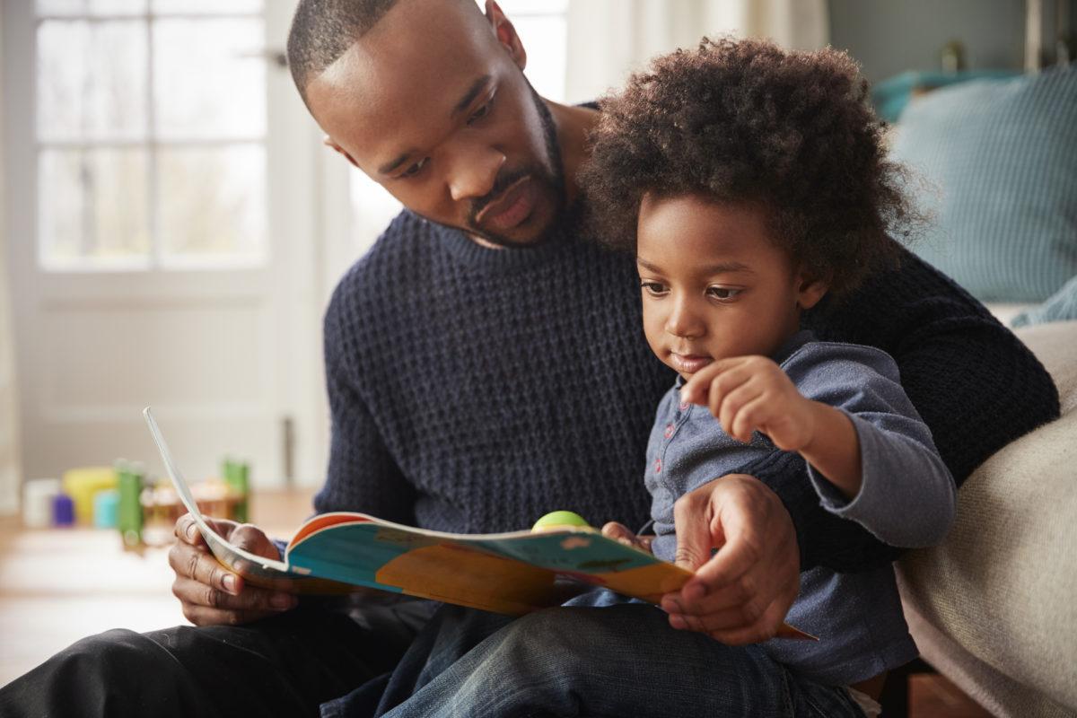 Vater liest Buch mit Sohn
