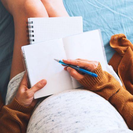 Schwangere Frau macht sich Notizen