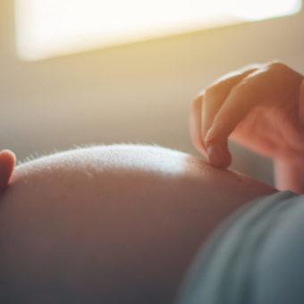 Schwangere Frau streichelt ihren Bauch
