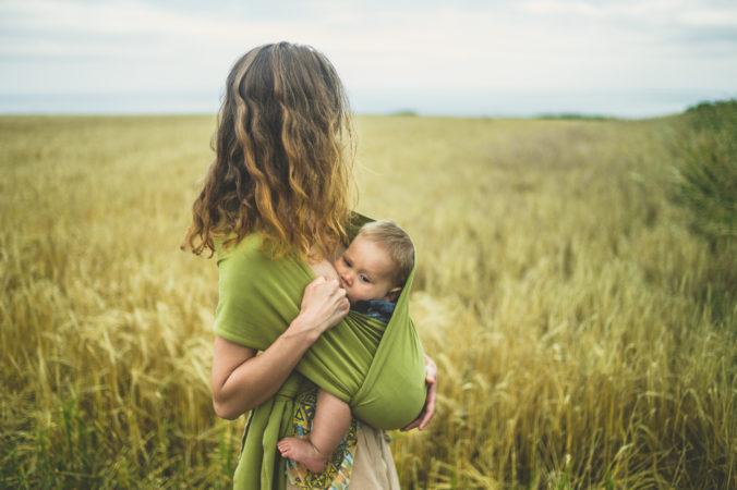 Mama stillt Baby auf Wiese
