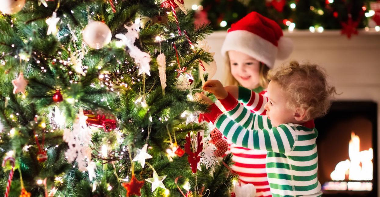 Kinder dekorieren Weihnachtsbaum