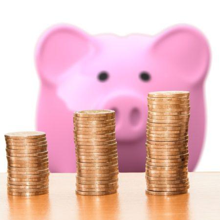 Sparschwein mit Münzen davor
