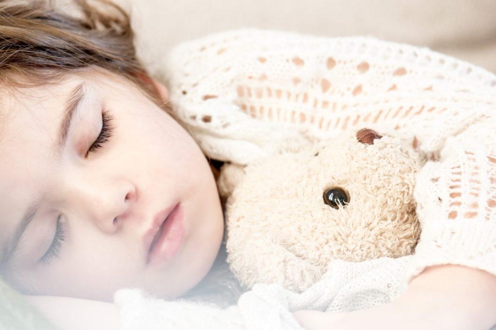Kind schläft mit Teddy