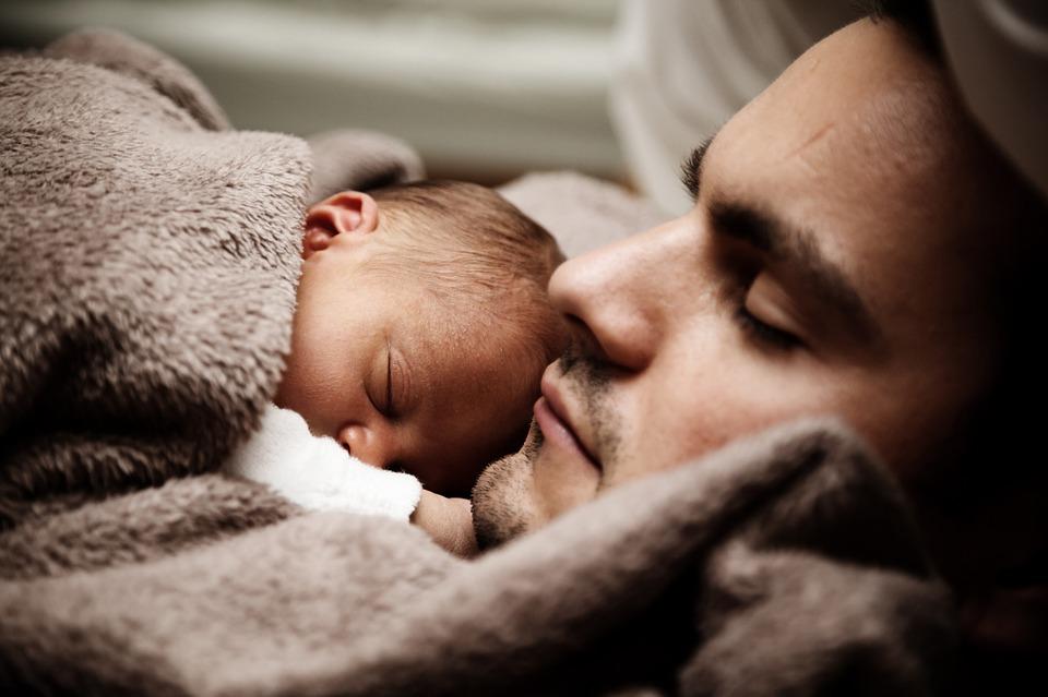 Papa mit schlafendem Baby auf dem Bauch