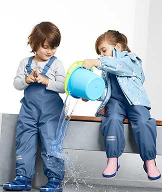 Zwei Kinder spielen in Regenkleidung