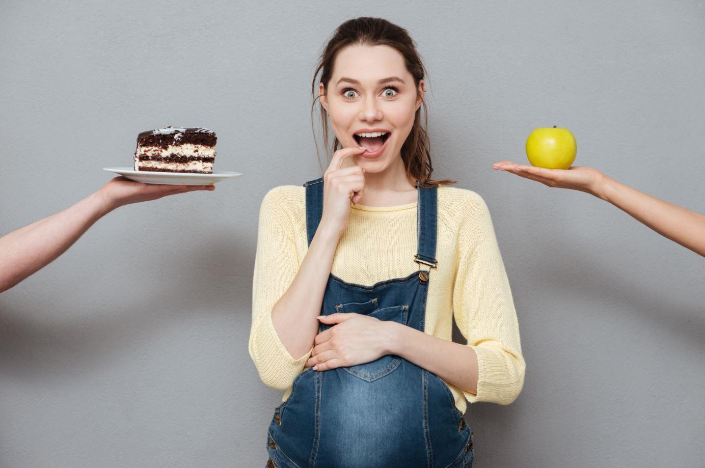 Schwangere Frau zwischen Kuchen und Apfel
