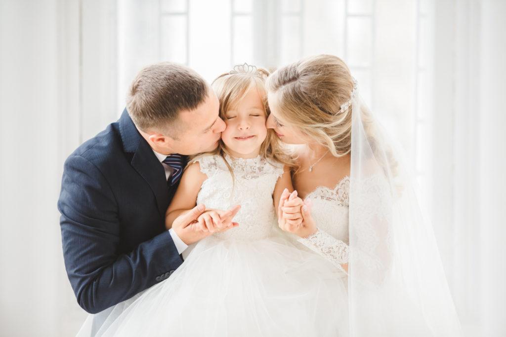 Stiefeltern umarmen Tochter auf Hochzeit