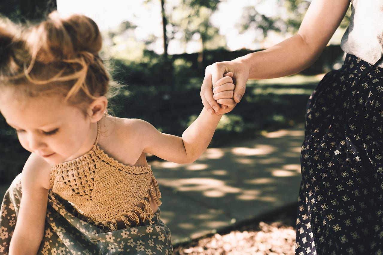 Kind läuft an Mamas Hand