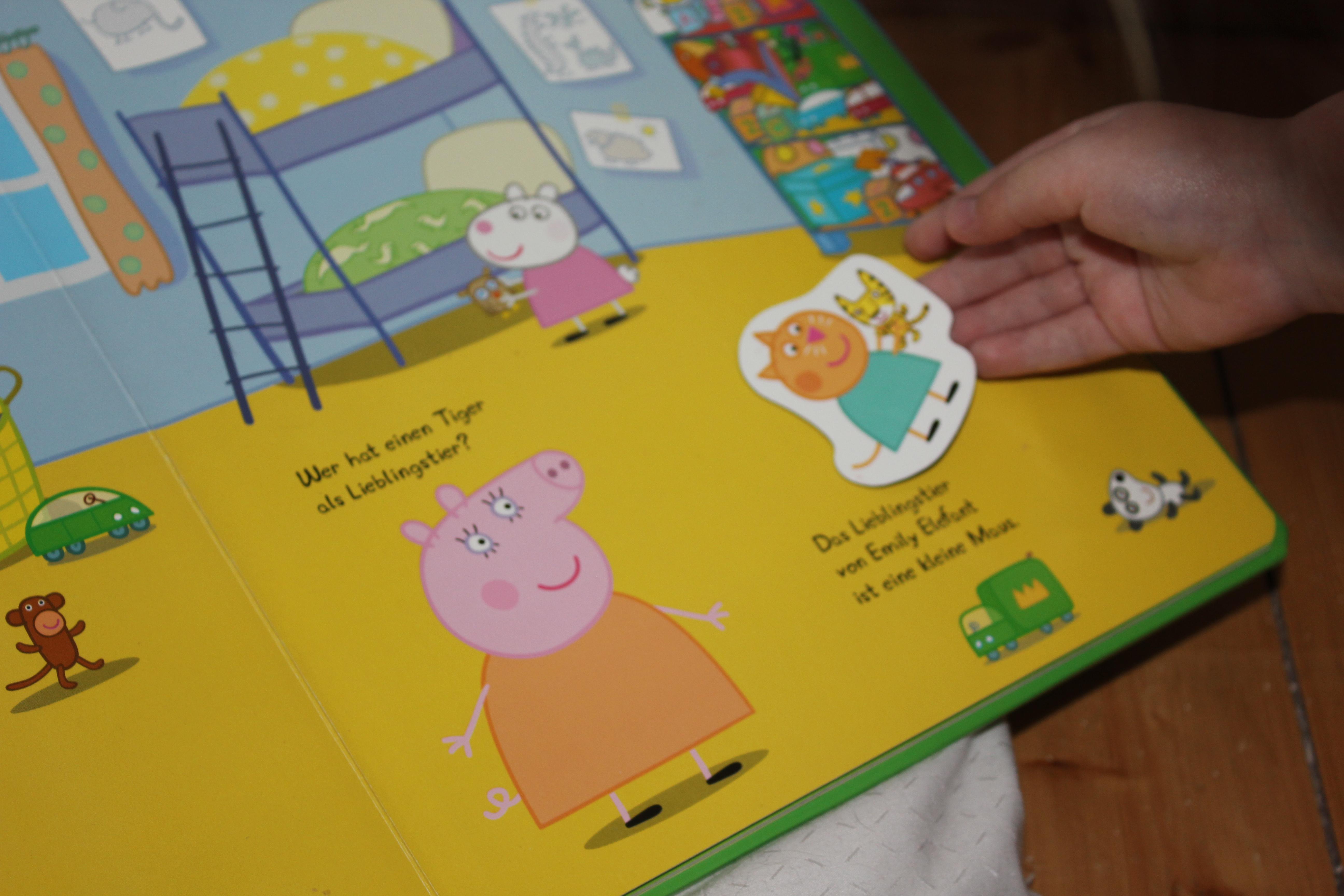 Kind legt Molly Mieze in das Peppa Wutz Buch