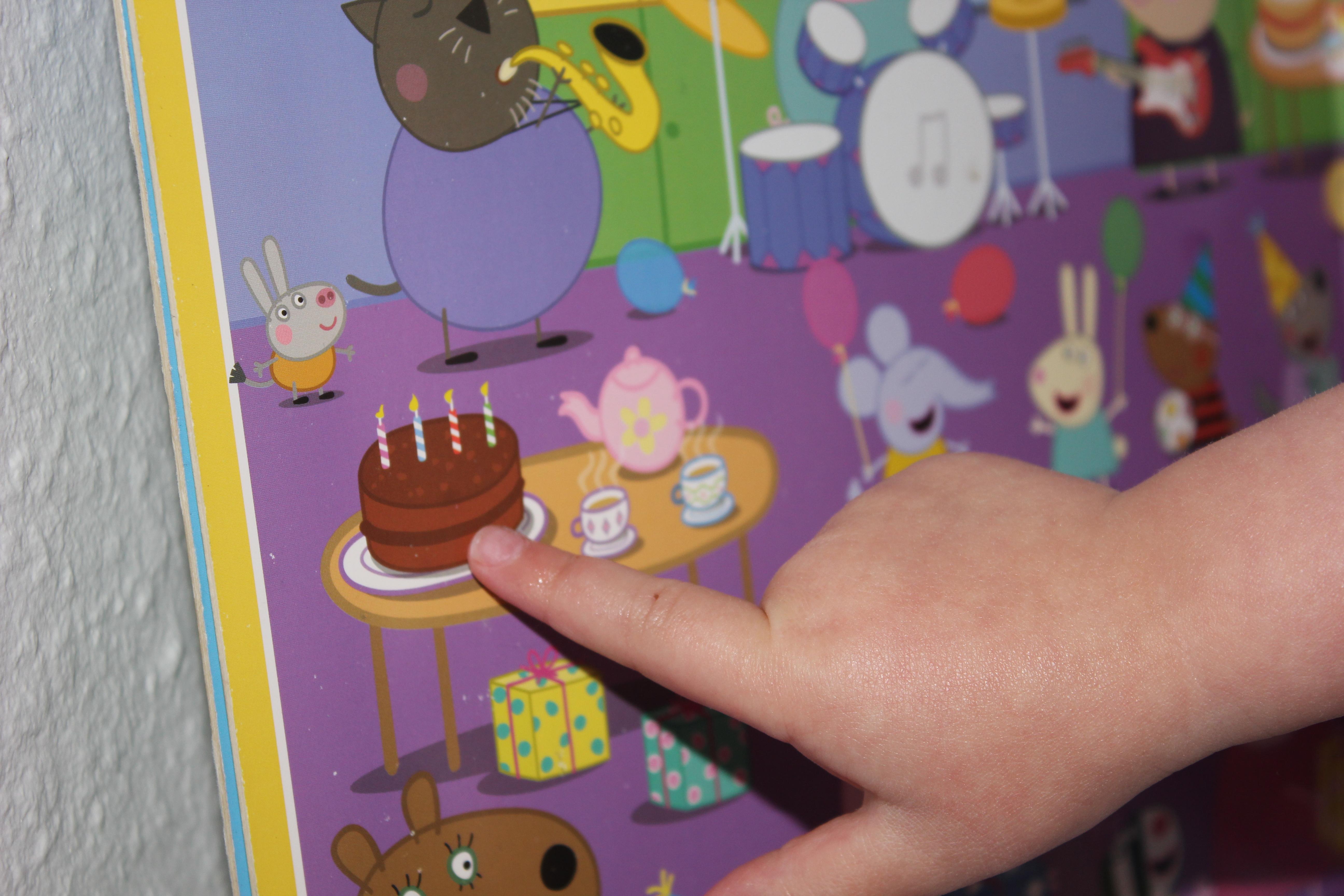 Kind zeigt auf den Kuchen im Peppa Wutz Wimmelbuch
