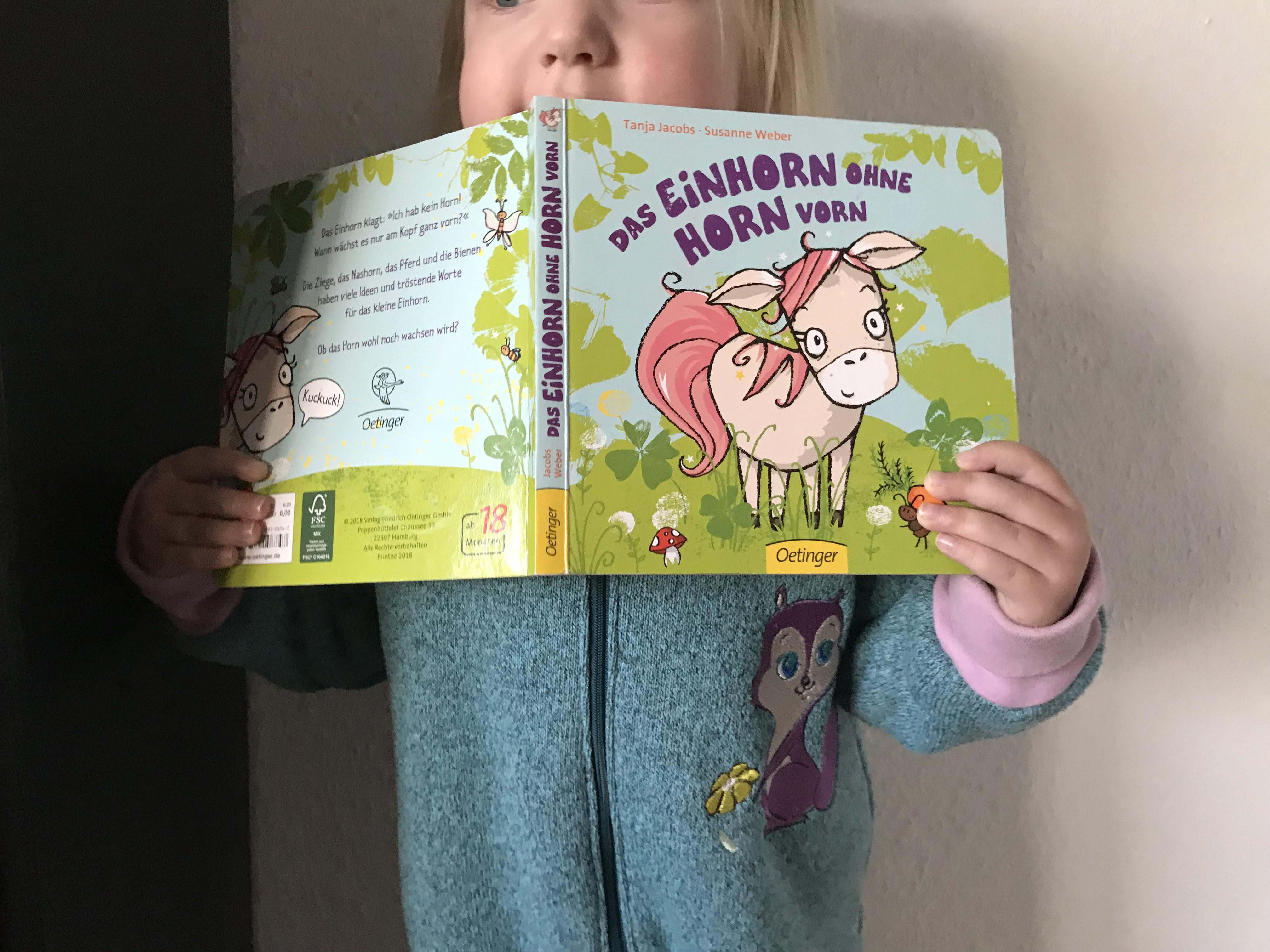 Kind hält Das Einhorn ohne Horn vorn-Buch fest