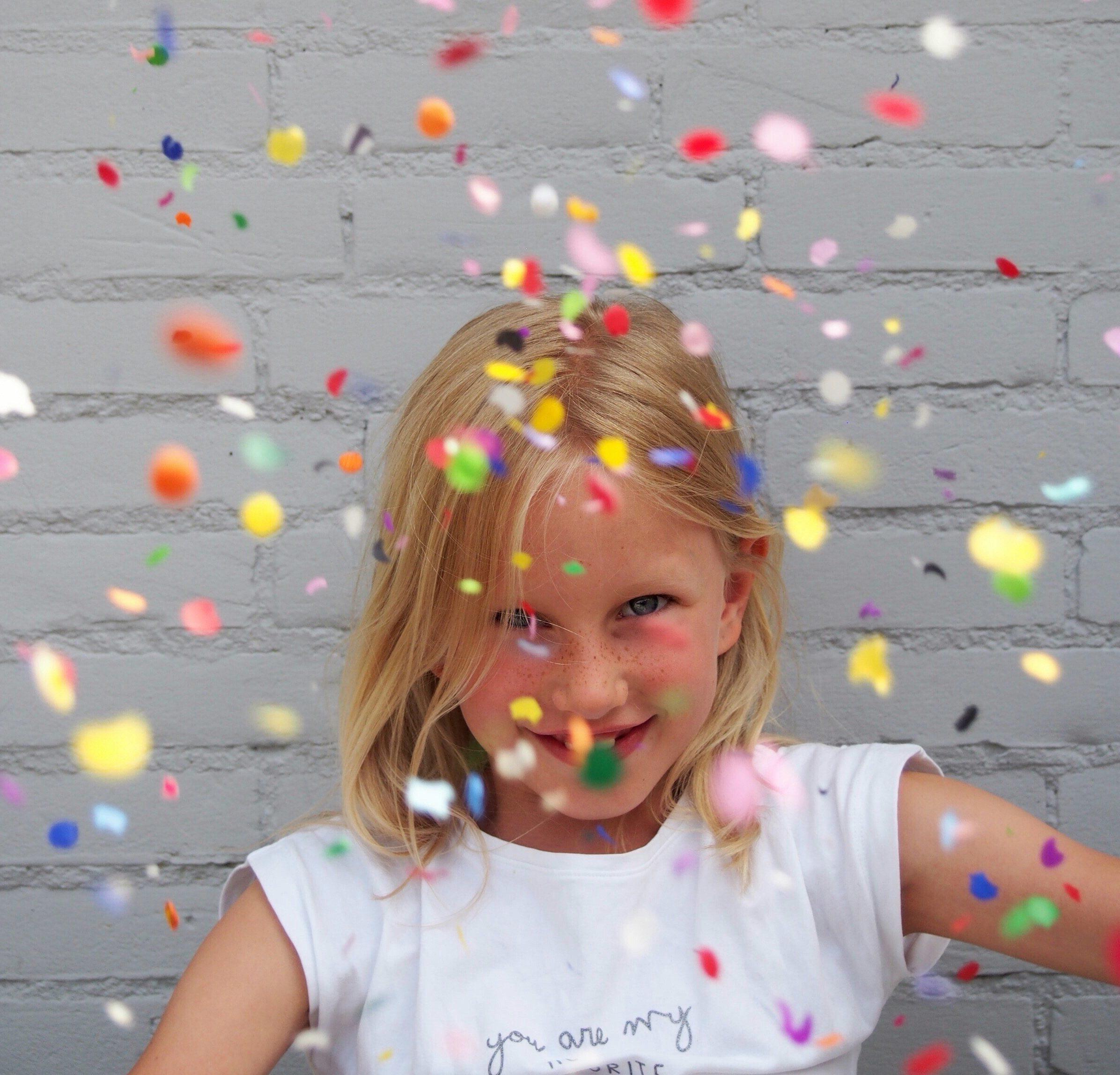 Kind feiert mit Konfetti