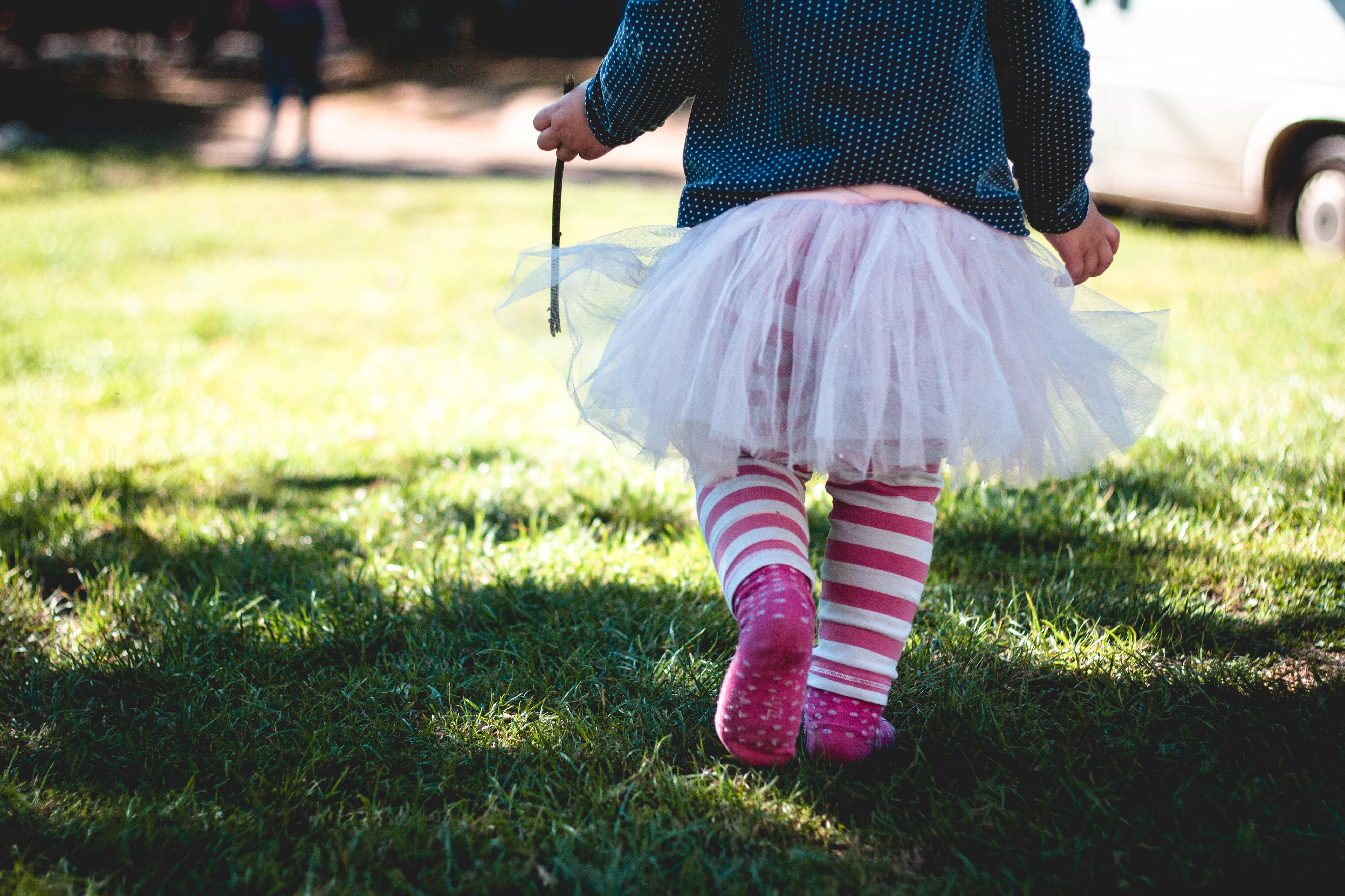 Mädchen mit Röckchen läuft durchs Gras