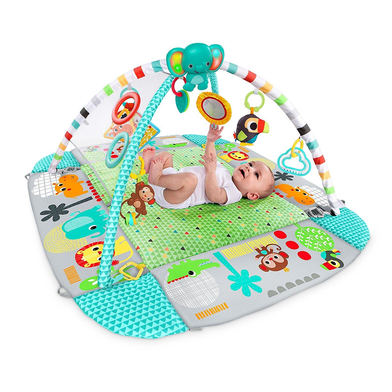 Baby liegt auf dem Rücken und spielt unter dem Spielbogen