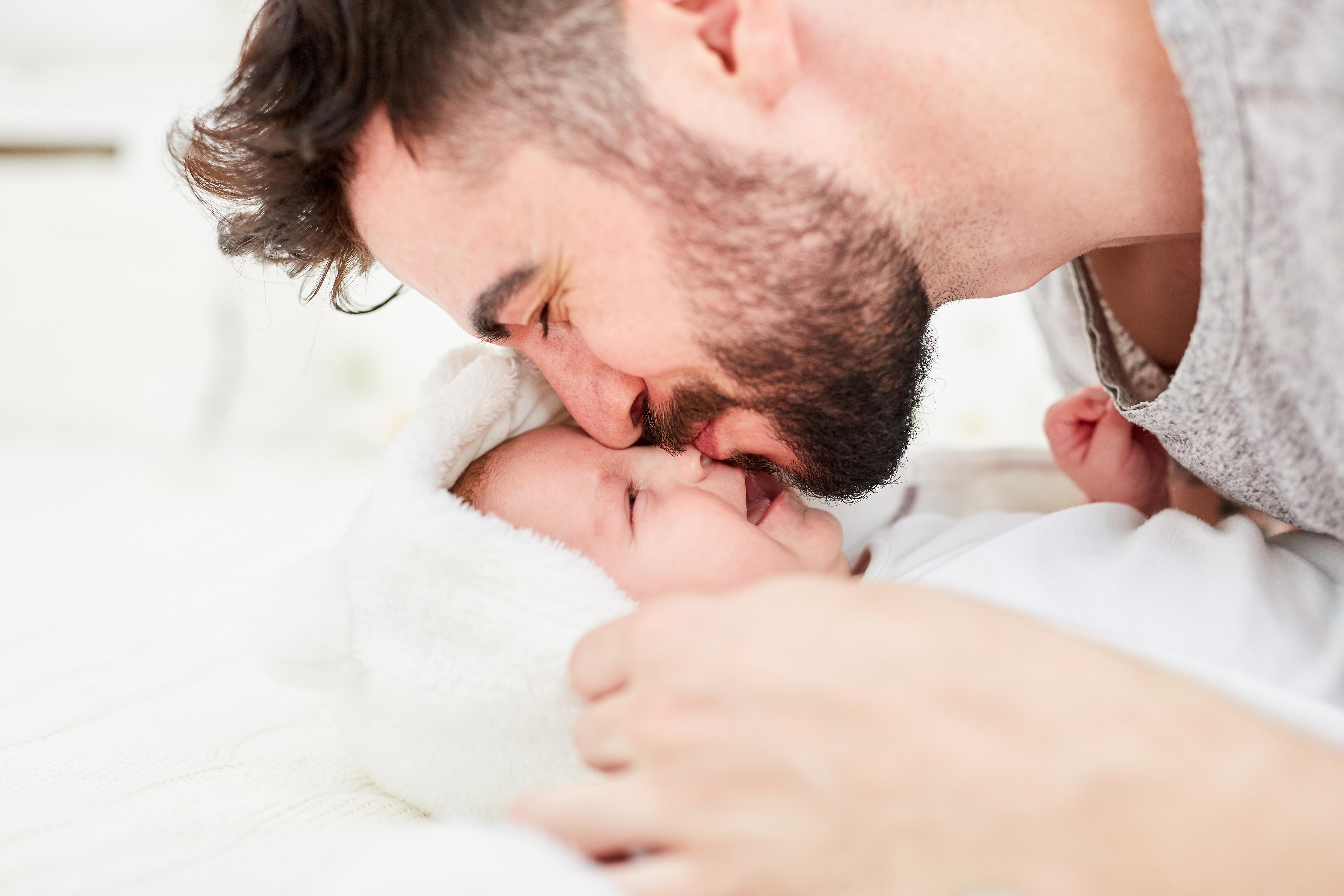 Glücklicher Vater gibt seinem neugeborenen Baby einen Kuss auf die Stirn