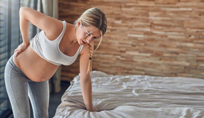 Schwangere Frau stützt sich auf Bett ab