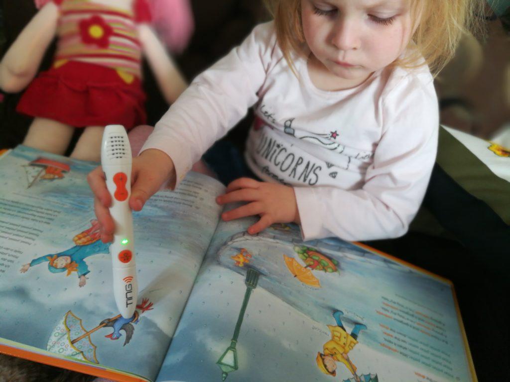 Kind schaut sich ein Buch mit dem TING Stift an
