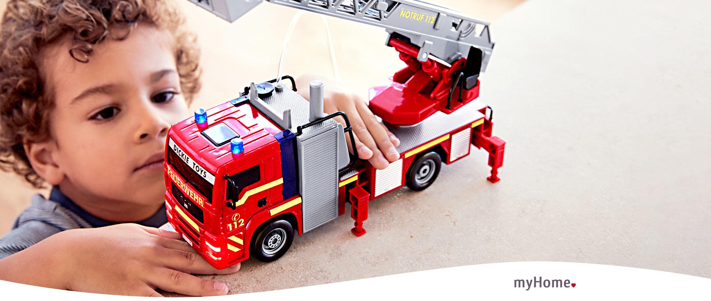 kleiner Junge spielt it Feuerwehrauto