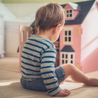 Junge vor Puppenhaus