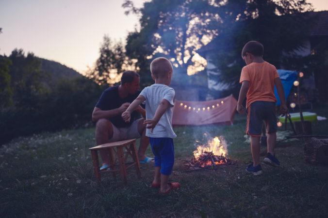 Familie sitzt in Abenddämmerung am Lagerfeuer