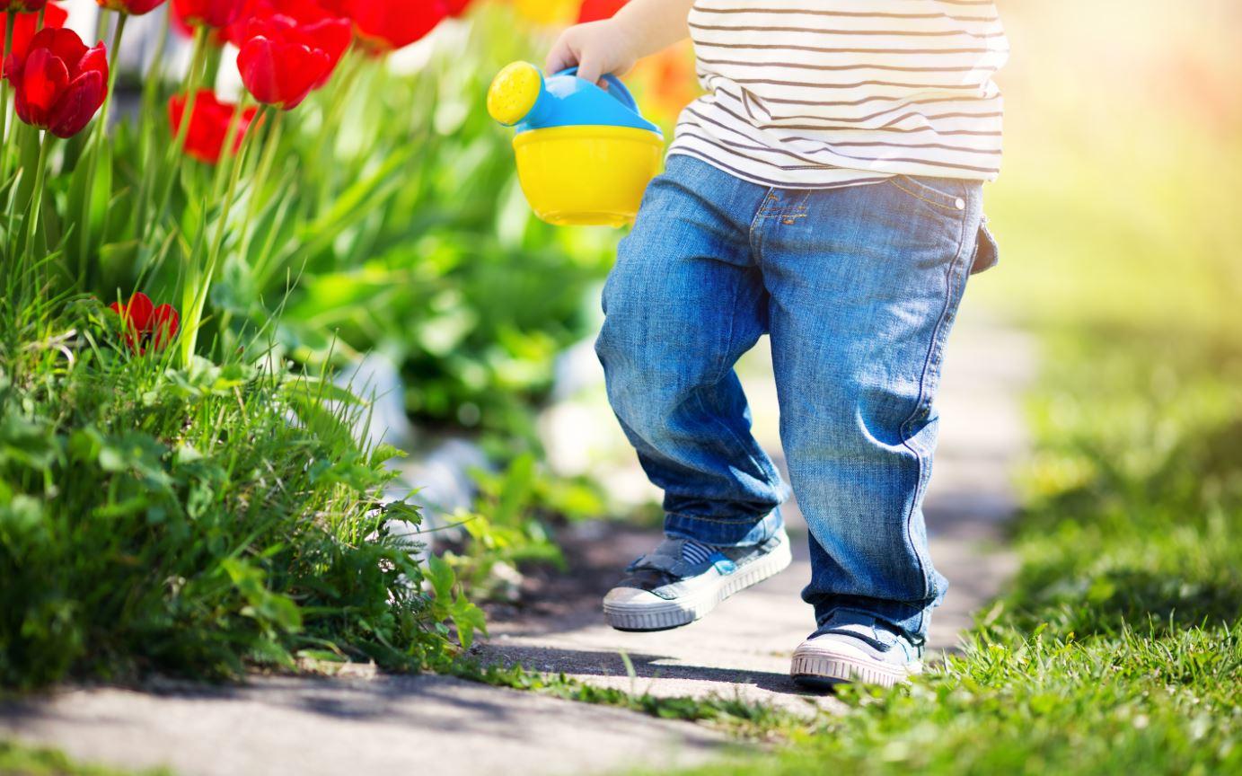 Kind mit kleine rGießkanne im Garten