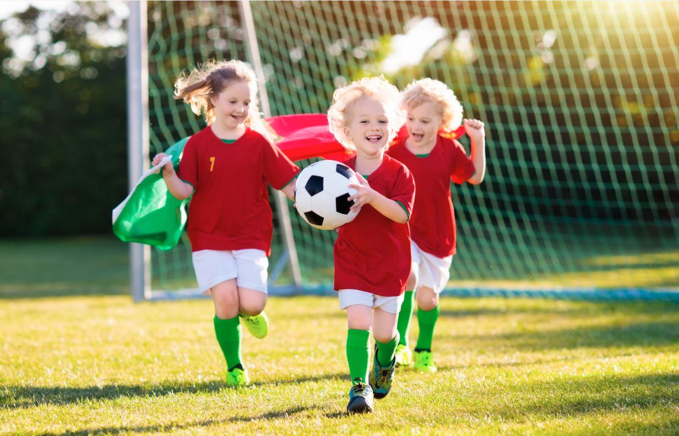 Jungs und Mädchen spielen zusammen Fußball