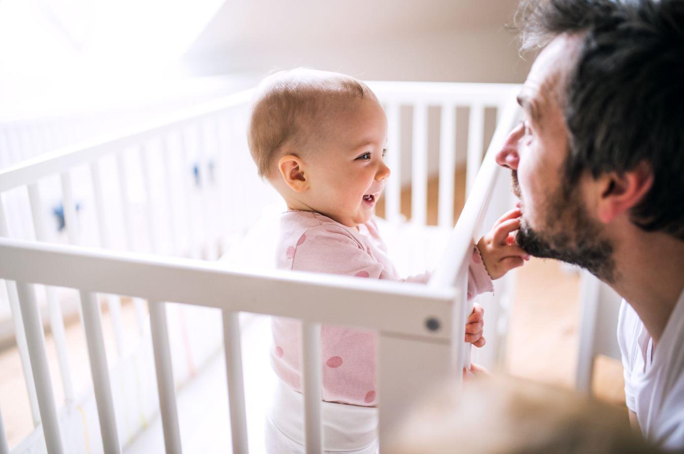 Kind im Babybett mit Papa davor