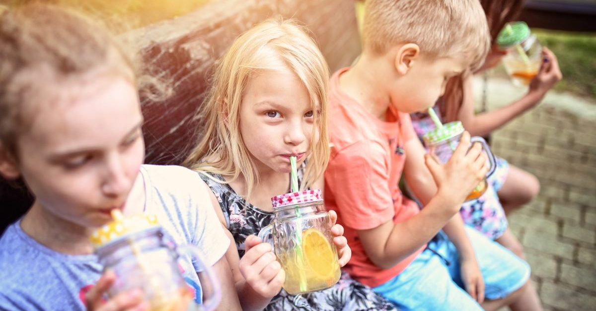 Kinder kühlen sich an einem heißen Tag mit Saft ab