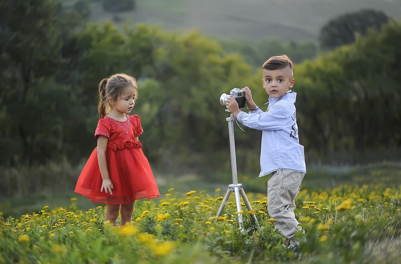 Junge fotografiert Mädchen im roten Kleid